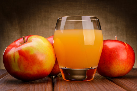 Glass of apple juice with apples on wood background photo