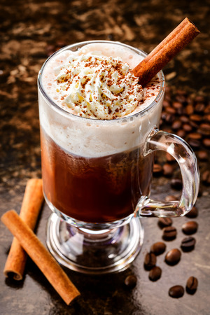 Irish coffee with cinamon among coffee beans