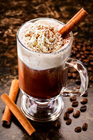 Irish coffee with cinamon among coffee beans