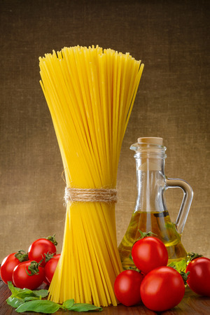 Bundle of spaghetti with basil, tomato and a jar of olive oil photo