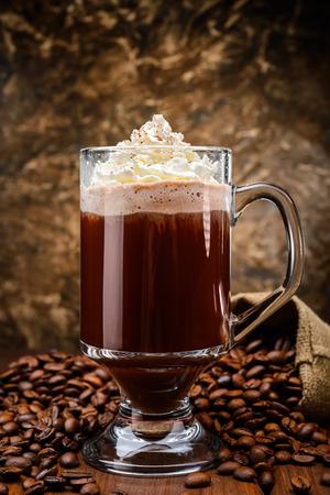Irish coffee on wooden table among coffee beans