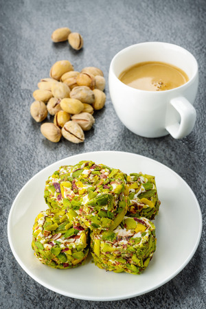 Turkish pistachio dessert with a some of pistachios and coffee. Toned image photo