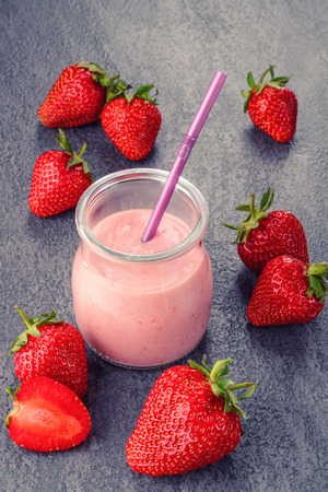 Closeup of strawberry fruit smoothies with strawberry pieces in glass with straw photo