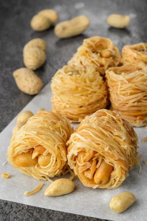 Closeup of birds nest baklava dessert with peanuts. Selective focus photo