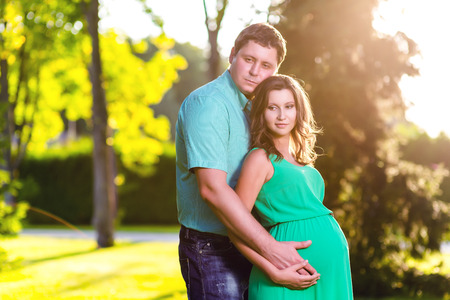 Happy and young pregnant couple hugging in nature photo