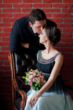 Bride and groom kissing on a red wall background photo
