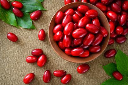 crimson colour: fresh cornel berries in brown bowl