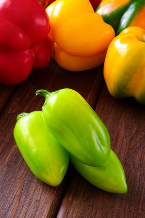 Colored bell peppers on wooden table photo