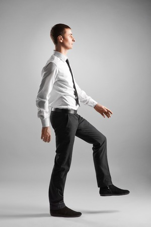 business and education concept- businessman stepping on imaginary step photo