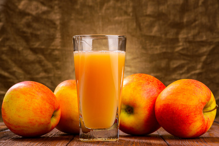 Glass of apple juice with apples on fabric background Stockfoto