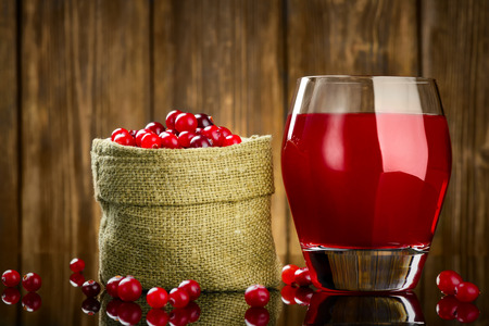 Fresh Organic Cranberry Juice against a wooden background photo