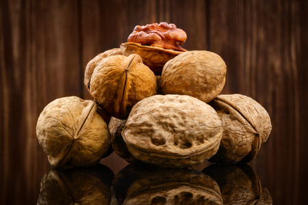 Walnut kernels and whole walnuts on rustic wooden background photo