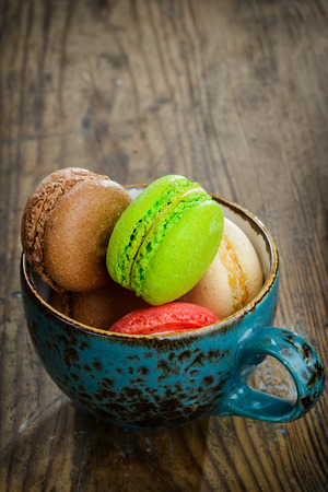 Sweet and colourful french macaroons on wooden background photo