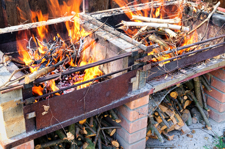 self made: Burning firewood in self made brick and metal brazier or grill