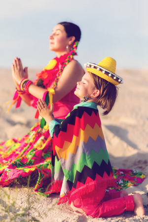 son of god: Toned photo of son and mother dressed in Mexican clothes praying together Stock Photo