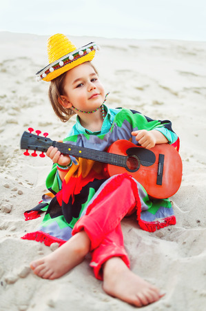 Photo teintée de Petit garçon sourire heureux joue de la guitare ou ukulélé Banque d'images