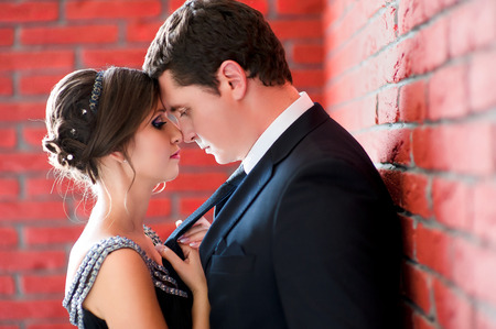 Bride and groom on a red wall background photo