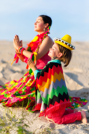 praying together: son and mother dressed in Mexican clothes praying together Stock Photo
