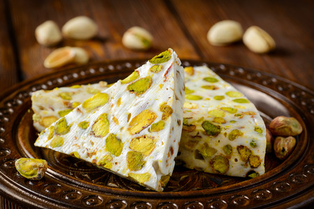 turkish dessert: Turkish delight. Arabic dessert with and Pistachios on wooden plate. Selective focus