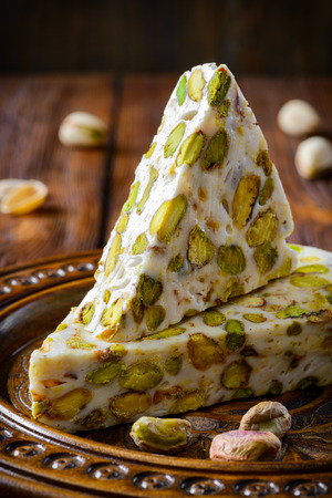 Turkish delight. Arabic dessert with and Pistachios on wooden plate. Selective focus photo