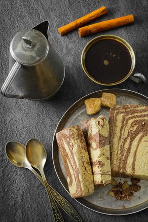 Slice of chocolate Greek halva on metal plate and coffee. Eastern dessert