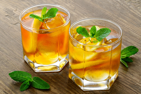 thirst quenching: lemon ice tea on brown wooden table with lemons around Stock Photo