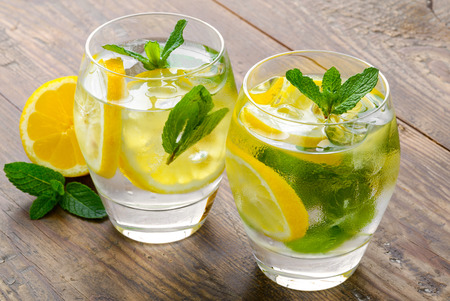 Lemon coctail drink. Lemonade in two glass and lemon with mint on the table