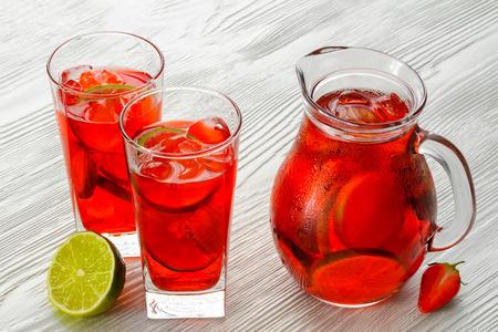 Coctail. Verfrissende zomer drinken met aardbei in kruik en glas op witte houten tafel