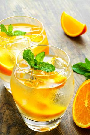 Des boissons fraîches avec de la glace et de la menthe. Orange cocktail sur la table en bois rustique