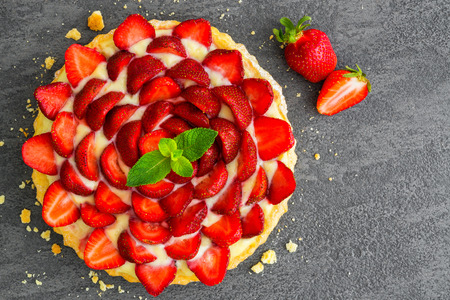 overhead view of fresh strawberry pie or tart with berries on gray background