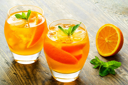 jugo de frutas: Cocktail. Zumo de naranja con la menta y el hielo mesa de madera rústica