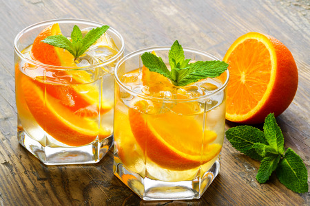 cocktail: Cold drinks with ice and mint. Orange cocktail on rustic wooden table