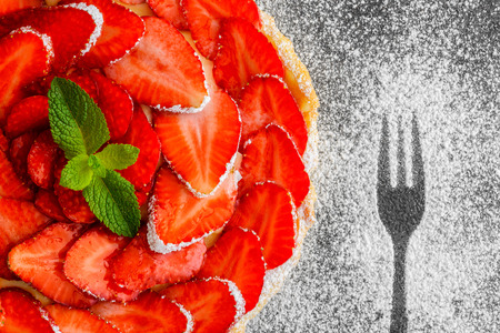 tart with cream and fresh strawberries on the  gray background, top view photo