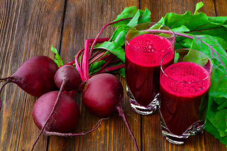 fresh vegetable: Glass of fresh beetroot juice with bets on wooden table. Stock Photo