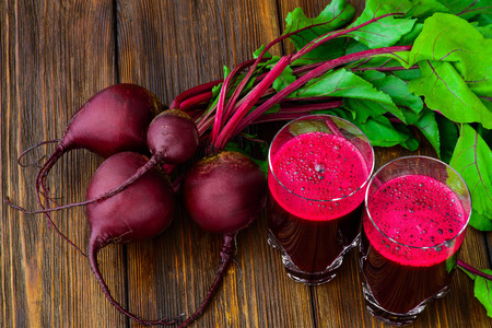 Glass of fresh beetroot juice with bets on wooden table. Stockfoto