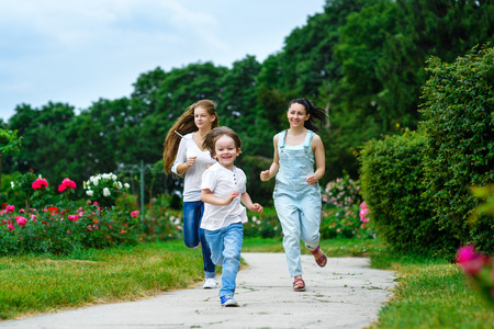 scamper: Happy Mother with daughter and son running on grass smiling.