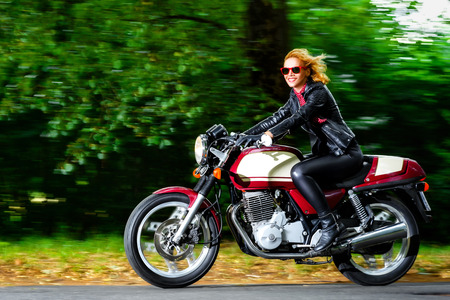Active woman riding on the motorbike, slow motion, having fun in bikers tour, vintage style photo, happy adventure concept