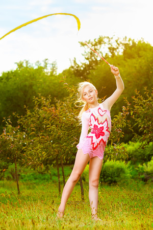 warms: Young gymnast warms up with a gymnastic tape or feed. Stock Photo