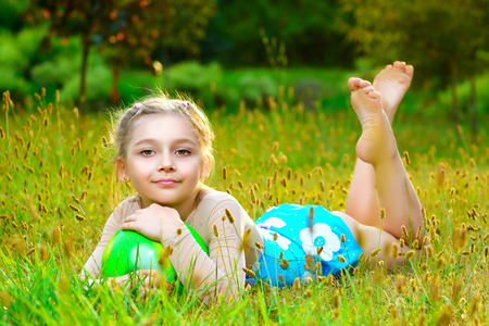 splits: outdoor portrait of young cute little girl gymnast training with ball on grass.
