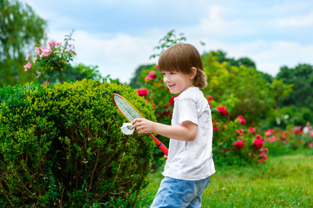 badminton: Play badminton. Portrait of happy little boy holding badminton racket and shuttlecock while standing on green grass.
