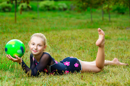 outdoor portrait of young cute little girl gymnast training with ball on grass.