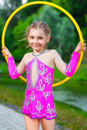 fitness, sport, les gens et le concept de soins de santé - petite fille sportive exercice avec hula hoop sur le parc arrière-plan.
