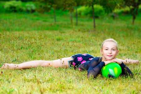 acrobat gymnast: flexible little blondie girl doing gymnastics horizontal split.