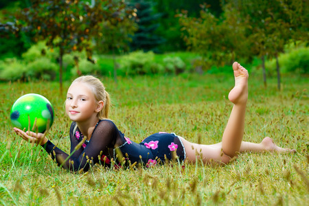 gym ball: outdoor portrait of young cute little girl gymnast training with ball on grass.
