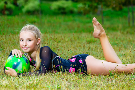 flexible: outdoor portrait of young cute little girl gymnast training with ball on grass.
