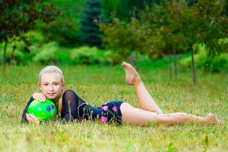 al aire libre retrato de la joven poco entrenamiento linda muchacha del gimnasta con la bola en hierba.