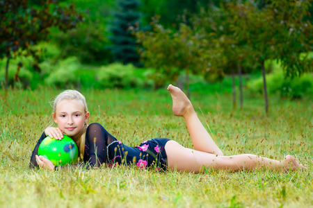 gymnastic: outdoor portrait of young cute little girl gymnast training with ball on grass.