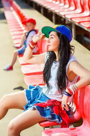 hot boy: Rapper attitude rap singer hip Hop Dancer performing. Stylish woman and little boy sitting in the stands of stadium. Stock Photo