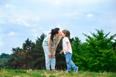 cheek: Loving son kissing his happy mother on the cheek. Stock Photo