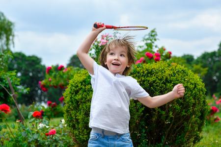 Jouer au badminton. Portrait de l'heureux petit garçon tenant raquette de badminton et volant en sautant.